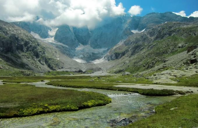 Pradera a los pies del Macizo y Glaciar del Vignemale con el río Oulettes de Vignemale formando pequeños meandros