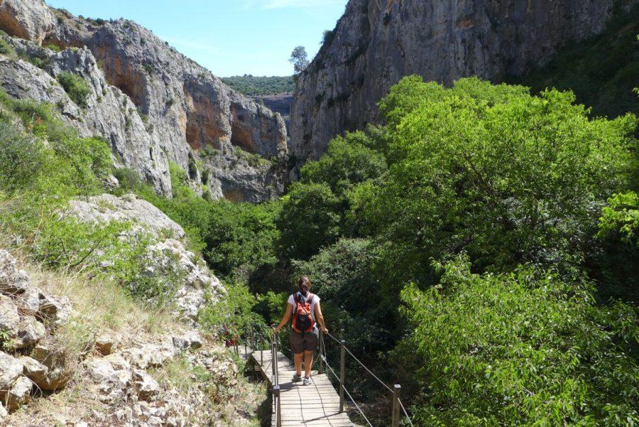 primeras pasarelas de madera que bajan encajonadas entre la Peña Castibián, a la izquierda, y los Muros de la Colegiata, a la derecha.
